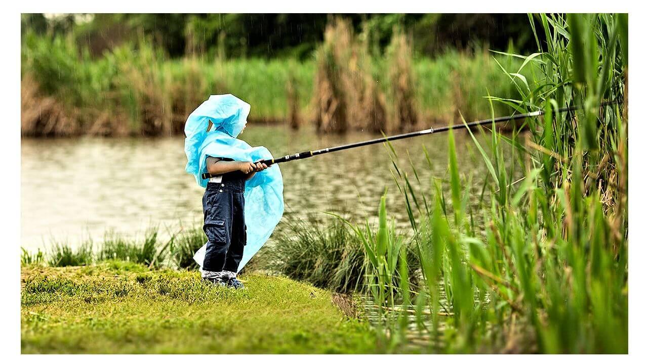Иллюстрация к записи Ребенок в дождивике ловит рыбу
